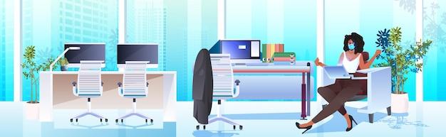 Geschäftsfrau in der maske, die am arbeitsplatz sitzt und das moderne büroinnenraum des laptop-coronavirus-pandemiekonzepts horizontal verwendet