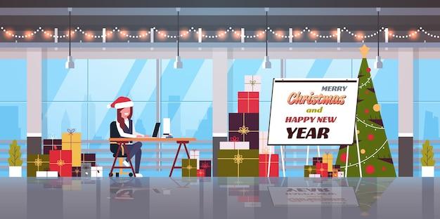 Geschäftsfrau in der weihnachtsmannmütze, die am arbeitsplatz geschäftsfrau mit laptop frohe weihnachten frohes neues jahr winterferien feier konzept moderne büroinnenwohnung sitzt
