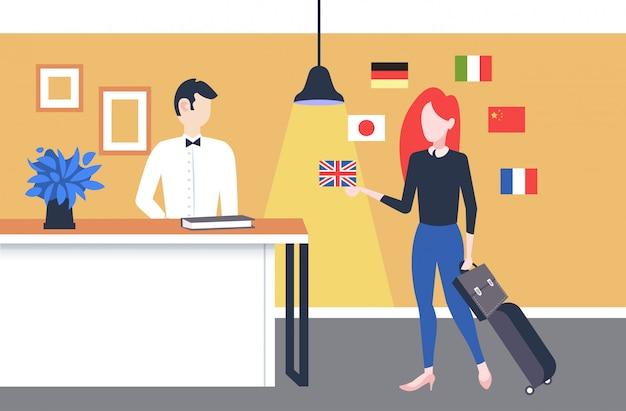 Geschäftsfrau kommt zum hotelempfangsmädchen unter verwendung des mobilen app-wörterbuchs oder des übersetzers an, die mit empfangsmitarbeiter-verbindungskonzept verschiedene sprachenfahnen in voller länge horizontal diskutieren