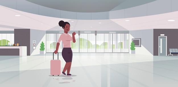 Geschäftsfrau mit modernem empfangsbereich des gepäcks afroamerikanische geschäftsfrau, die koffer hält, der im innenraum des zeitgenössischen hotelhall der lobby steht