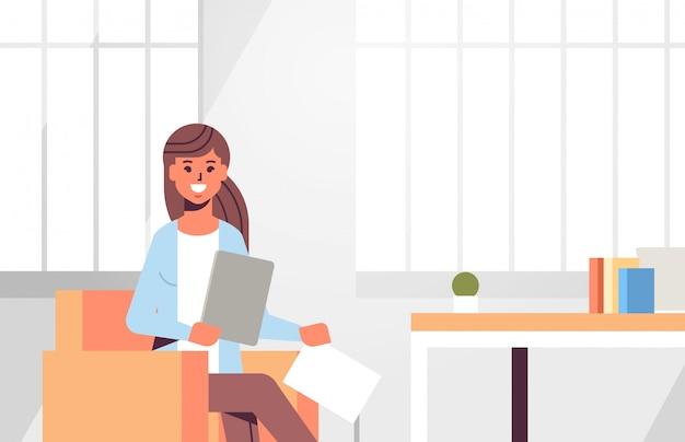 Geschäftsfrau sitzt am arbeitsplatz schreibtisch geschäftsfrau mit papierdokumenten, die berichtarbeitsprozess moderne büroinnennahaufnahme vorbereiten