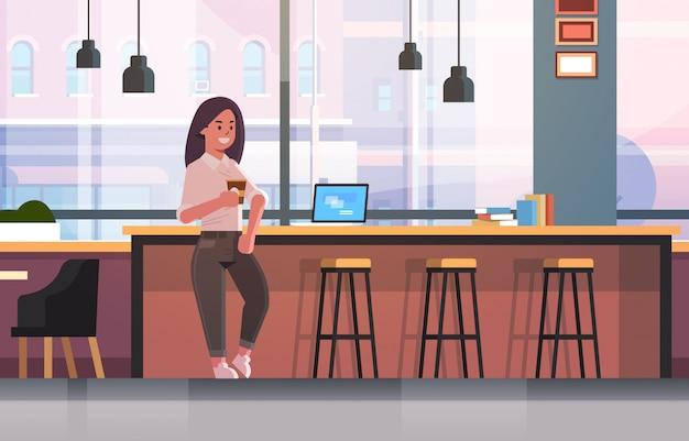 Geschäftsfrau sitzt auf stuhl am bartheke mit laptop-kaffeepause-geschäftsfrau, die cappuccino modernes café-interieur trinkt
