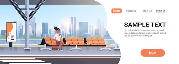 Geschäftsfrau sitzt moderne bushaltestelle frau, die zeit wartet, die öffentliche verkehrsmittel auf flughafenbahn-stadtbildhintergrund horizontal in voller länge kopienraum wartet