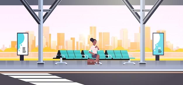 Geschäftsfrau sitzt moderne bushaltestelle frau, die zeit wartet, die öffentliche verkehrsmittel auf flughafenbahn-stadtbildhintergrund horizontal in voller länge wartet