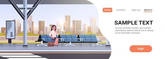 Geschäftsfrau sitzt moderne bushaltestelle geschäftsfrau mit koffer, die öffentliche verkehrsmittel auf stadtbild der flughafenstation wartet