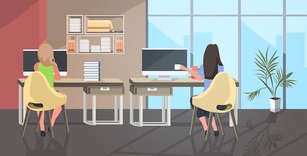 Geschäftsfrauenpaar sitzt am arbeitsplatz schreibtisch geschäftsfrauen mit computer trinken kaffee coworking center modernen offenen raum büro interieur
