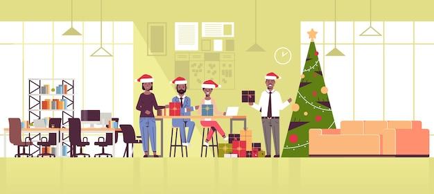 Geschäftsleute, die firmenfeiermitarbeiter feiern, die geschenkgeschenkboxen halten frohe weihnachten frohes neues jahr winterferienkonzept moderne büroeinrichtung