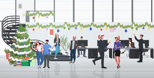 Geschäftsleute, die firmenpartymitarbeiter feiern, die champagner frohe weihnachten frohes neues jahr winterferienkonzept modernes bürointerieur trinken