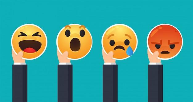 Geschäftsleute, die ihre hände heben, um gefühle durch das gesicht von cartoon emoji auszudrücken.
