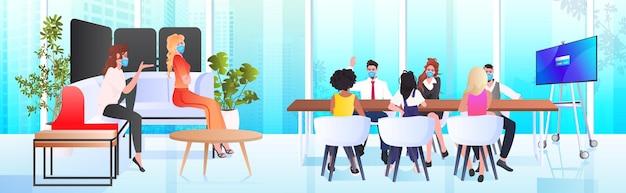 Geschäftsleute in masken, die zusammen arbeiten und im coworking center coronavirus-pandemie-teamarbeitskonzept modernes büroinnenraum horizontal in voller länge sprechen