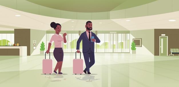 Geschäftsleute mit gepäckpaar, das am empfangsbereich afroamerikaner-geschäftsmannfrau steht, die koffer zeitgenössische lobby-hotelhalle innenraum hält