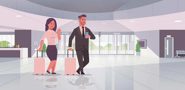 Geschäftsleute mit gepäckpaar, das an der empfangsbereich-geschäftsmannfrau steht, die koffer zeitgenössische lobby-hotelhalle innenraum hält