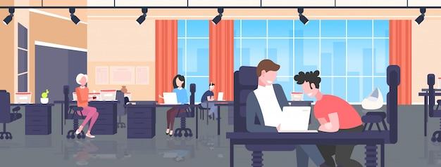 Geschäftsleute sitzen am arbeitsplatz schreibtisch geschäftsleute mit laptop arbeitsprozess teamwork-konzept moderne büroeinrichtung horizontal in voller länge
