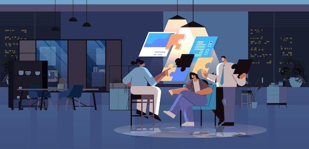 Geschäftsleute-team, das puzzleteile zusammensetzt problemlösung teamwork-konzept dunkle nacht büroinnenraum horizontal in voller länge