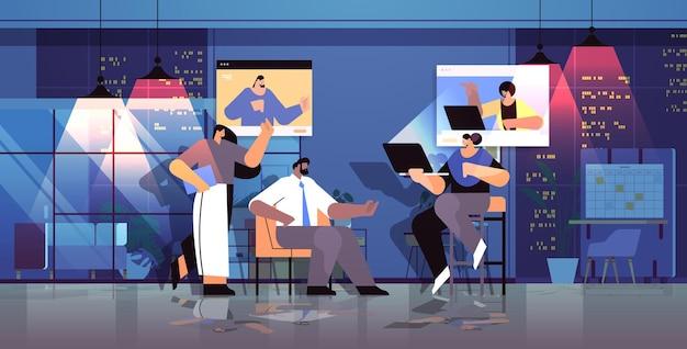Geschäftsleute-team diskutiert während des videoanrufs virtuelle konferenz online-kommunikation teamwork-konzept nachtbüroinnenraum horizontal in voller länge