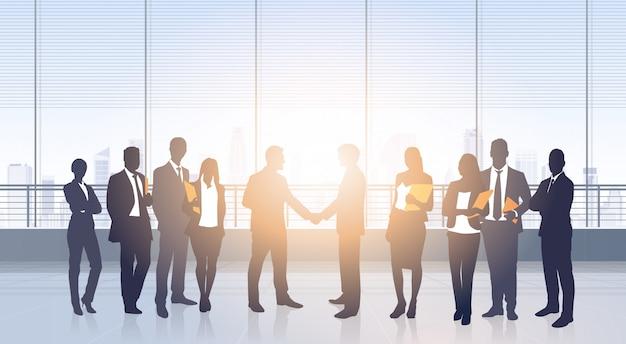Geschäftsleute treffen sitzungsvereinbarungs-handshake-silhouetten-modernen bürogebäude-innenraum