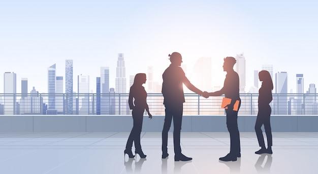 Geschäftsleute treffen sitzungsvereinbarungs-handshake-silhouetten-modernes stadt-ansicht-bürogebäude
