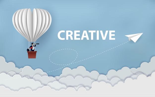 Geschäftsmann auf dem heißluftballon, der binokular hält