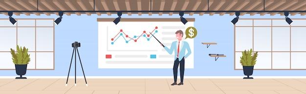 Geschäftsmann blogger erklärt diagramme finanzdiagramm geschäftsmann aufnahme online-video mit kamera auf stativ präsentation blogging-konzept moderne büro interieur in voller länge horizontal