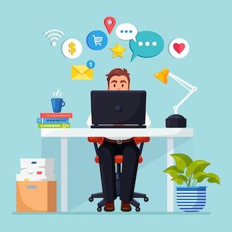 Geschäftsmann, der am schreibtisch mit sozialem netzwerk, mediensymbol arbeitet.