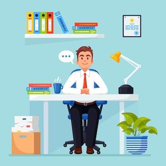 Geschäftsmann, der am schreibtischbüroinnenraum mit dokumentenkaffeemanager arbeitet, der auf stuhl sitzt