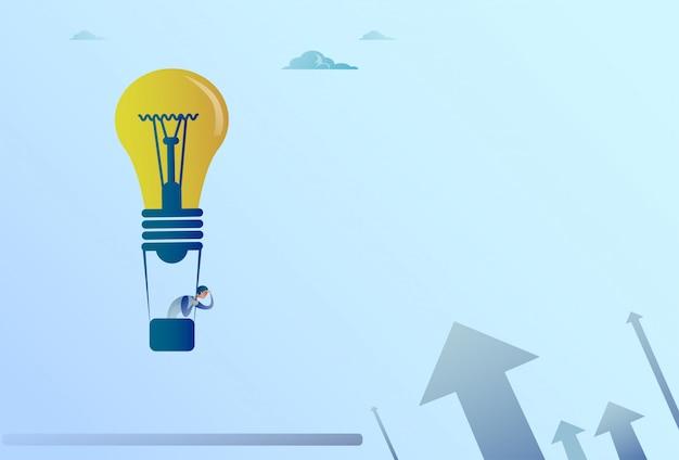 Geschäftsmann, der auf den glühlampe-luftballon fliegt, schaut mit fernglas auf pfeilen herauf finanzwachstum con