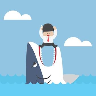 Geschäftsmann, der auf kiefern des haifischs steht