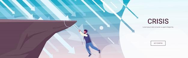 Geschäftsmann, der auf klippe von abgrundpfeilen klettert, die finanzkrise-konkurs-investitionsrisikokonzept-geschäftsmann fallen, der an seil in voller länge horizontalen kopienraum hängt