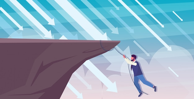 Geschäftsmann, der auf klippe von abgrundpfeilen klettert, die in finanzkrise fallen konkursinvestitionsrisikokonzept geschäftsmann, der am seil in voller länge horizontal hängt