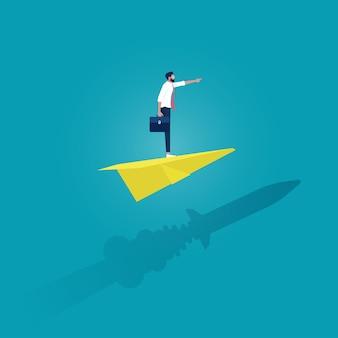 Geschäftsmann, der auf papierflugzeugen steht und mit raketenschatten über der wand fliegt