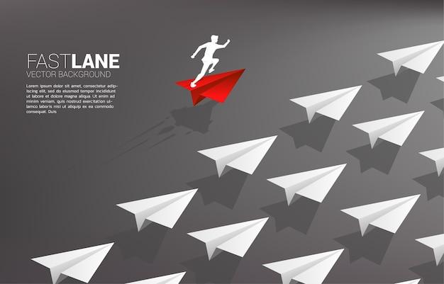 Geschäftsmann, der auf rotem origami-papierflugzeug läuft, bewegt sich schneller als gruppe von weiß. geschäftskonzept der überholspur für umzug und marketing