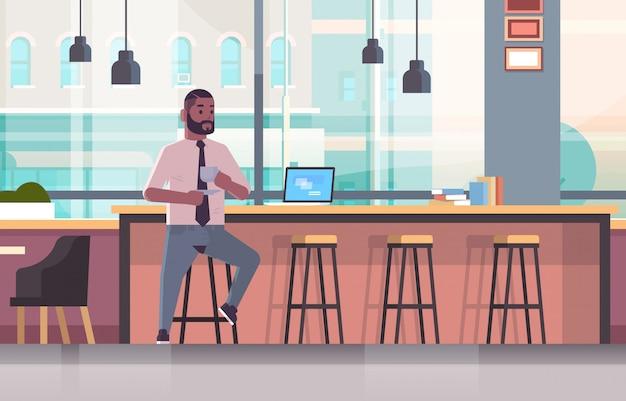 Geschäftsmann, der auf stuhl am bartheke mit laptop-kaffeepausenkonzeptgeschäftsmann sitzt, der cappuccino modernes caféinnenraum in voller länge horizontal trinkt