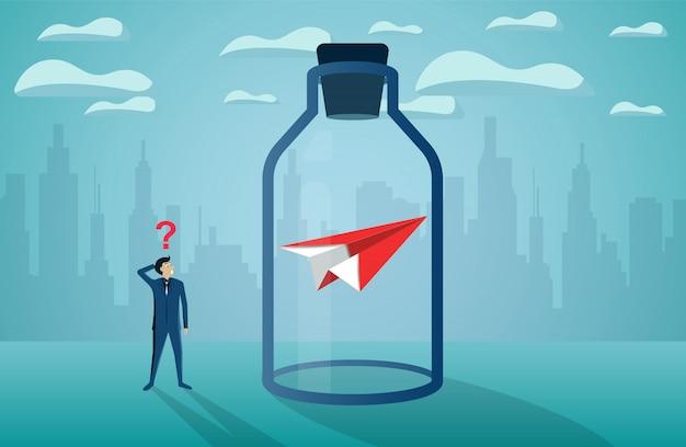 Geschäftsmann, der das rote papierflugzeug schauend fest in einer glasflasche steht