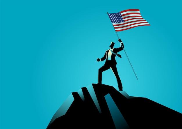 Geschäftsmann, der die flagge der usa oben auf dem berg hält