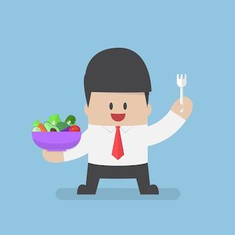 Geschäftsmann, der gemüsesalatschüssel und -gabel auf seiner hand hält