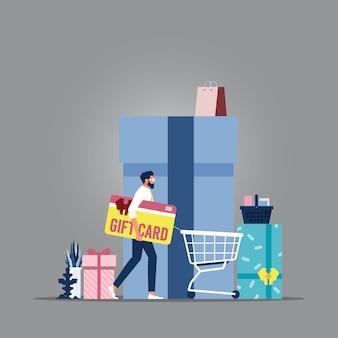 Geschäftsmann, der geschenkkarte mit einkaufswagen hält