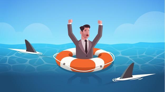 Geschäftsmann, der hände innerhalb des rettungsrings im wasser des hais erhebt, der hilft, das geschäft zu überleben, hilft beim horizontalen porträt des frustrationskonzepts der finanzkrise