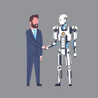 Geschäftsmann, der hände mit modernem roboter-künstlicher intelligenz-mechanismus-technologie-konzept rüttelt