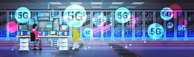 Geschäftsmann, der im rechenzentrumsraum-hosting-server 5g online-verbindungssystem des drahtlosen systems arbeitet mann, der am arbeitsplatzingenieur sitzt, der informationsdatenbank in voller länge horizontal überwacht