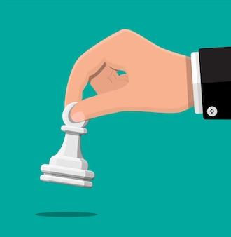 Geschäftsmann, der in der hand pwan schachfigur hält.