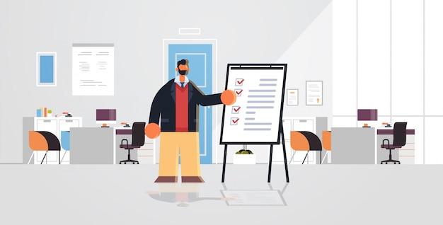 Geschäftsmann, der mit checkliste arbeitet geschäftsmann, der nahe flipchart mit fragebogenumfrageformular-testkonzept steht modernes büroinnenraum flach in voller länge horizontal