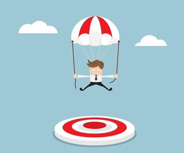 Geschäftsmann, der mit dem fallschirm fliegt, um anzuvisieren