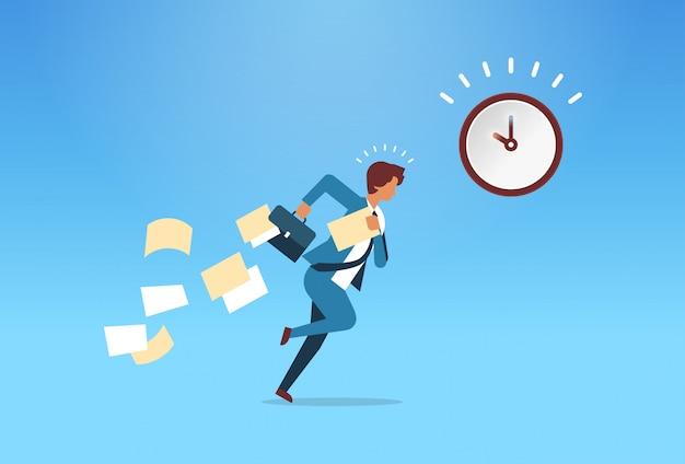 Geschäftsmann, der mit fallenden papieren von der aktenkofferzeitmanagementfrist läuft