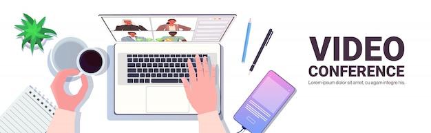 Geschäftsmann, der mit mischrassenkollegen während des videoanrufs geschäftsleute unterhält, die online-konferenzbesprechungskommunikationskonzept arbeitsplatz-schreibtischoberwinkelansicht-kopienraumillustration haben