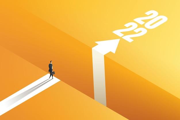 Geschäftsmann, der mit pfeilen am rand der lücke steht, um das ziel 2022 zu erreichen