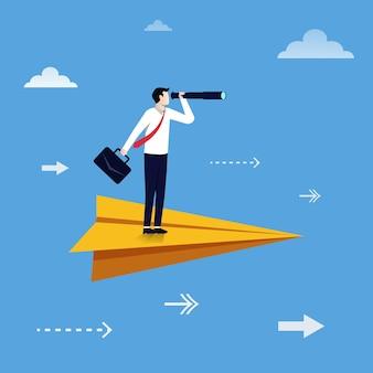 Geschäftsmann, der mit seinem fernglas auf einem flugzeugpapier steht. business vision konzept