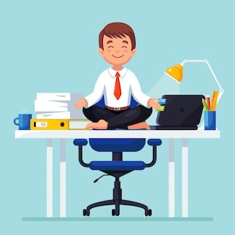 Geschäftsmann, der yoga am arbeitsplatz im büro tut. arbeiter sitzen in padmasana lotus pose auf dem schreibtisch, meditieren, entspannen, beruhigen und stress bewältigen.