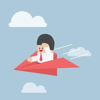 Geschäftsmann fliegt auf papierflugzeug und schaut vorwärts