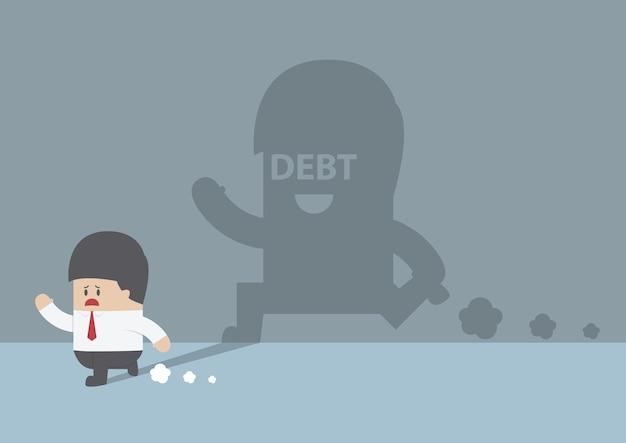 Geschäftsmann gefolgt von schuldenschatten