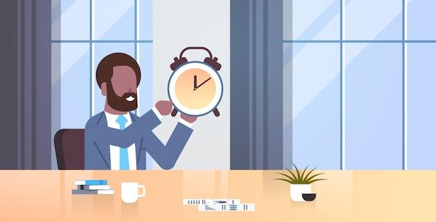 Geschäftsmann hält alarm antike uhr geschäftsmann sitzt arbeitsplatz schreibtisch frist zeitmanagement-konzept moderne büro interieur männliche charakter porträt wohnung